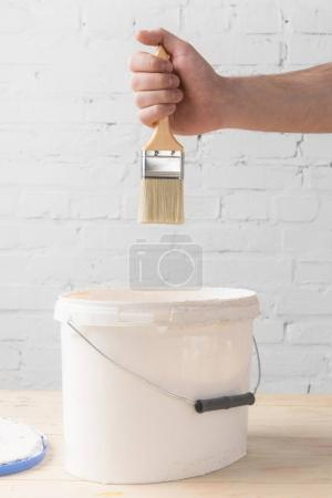 Photo for Cropped image of man holding brush in white paint above bucket - Royalty Free Image