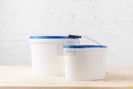 two plastic buckets with paints on wooden surface
