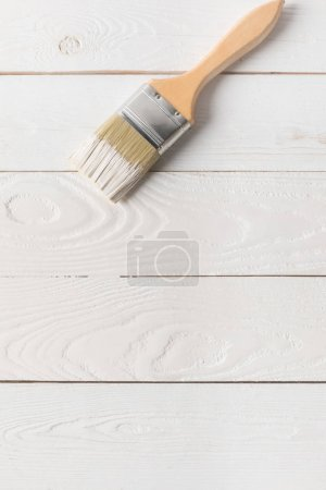 top view of brush in white paint on painted wooden surface