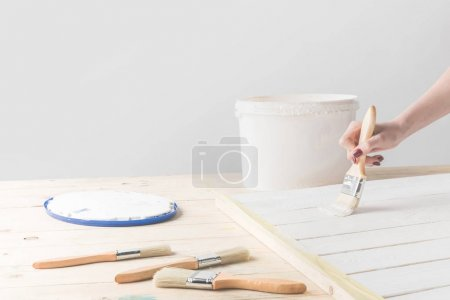 cropped image of girl painting wooden surface with white paint