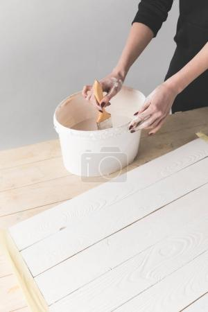cropped image of woman putting brush into white paint