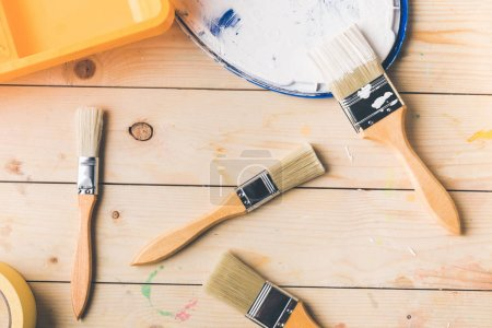 top view of different brushes and plastic tray on wooden surface