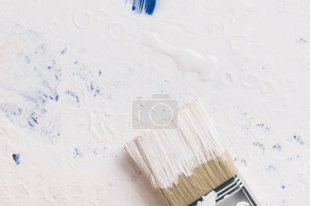 top view of brush in white paint on cover from bucket