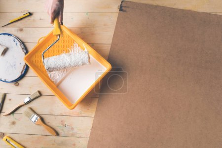 cropped image of woman putting paint roll brush in white paint
