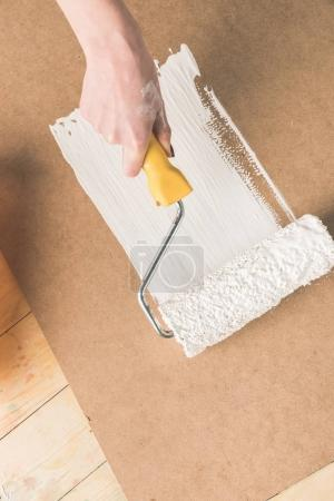 cropped image of woman painting plywood with paint roll brush