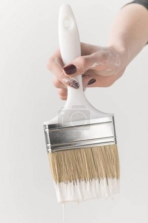 cropped image of girl holding brush in white paint isolated on white