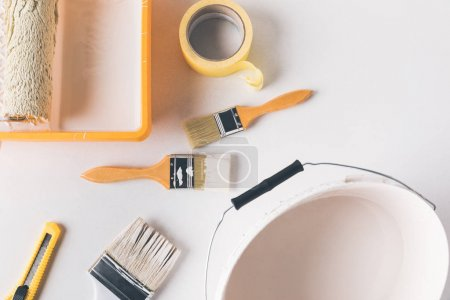 Photo for Top view of bucket with white paint and different tools for repairs on surface - Royalty Free Image