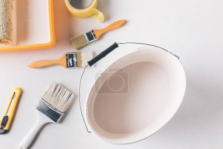 vue du dessus du seau avec peinture blanche et outils pour les réparations sur la surface