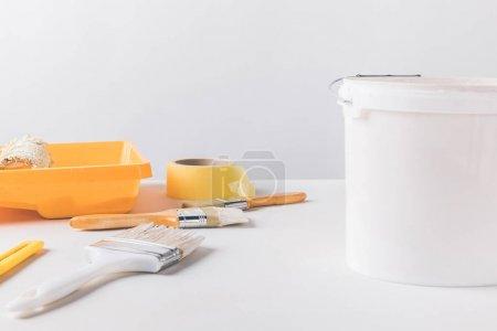 cubo con pintura y herramientas para reparaciones en superficie