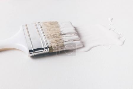 ein Pinsel in weißer Farbe auf weiß isolierter Oberfläche