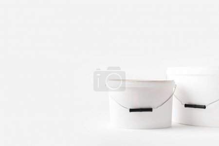 two plastic white buckets with paints isolated on white