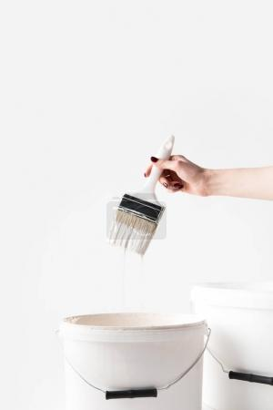 cropped image of woman holding brush in white paint above buckets isolated on white
