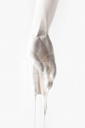cropped image of female hand in white dripping paint isolated on white