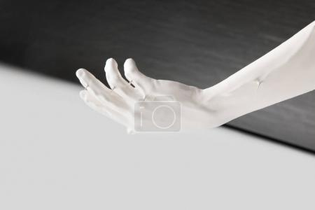 cropped image of female hand in white paint above black and white surface