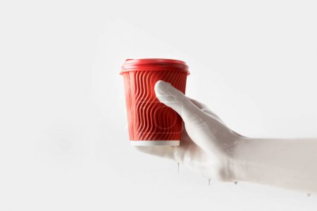 cropped image of woman in white paint holding red disposable coffee cup isolated on white