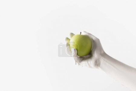 cropped image of woman in white paint holding green apple isolated on white
