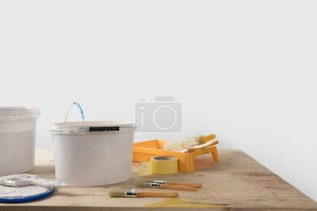 buckets with paints and plastic tray on wooden table