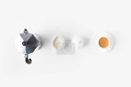 Photo pour Vue de dessus de tasse de café arrangée, jag de lait et cafetière sur la surface blanche - image libre de droit