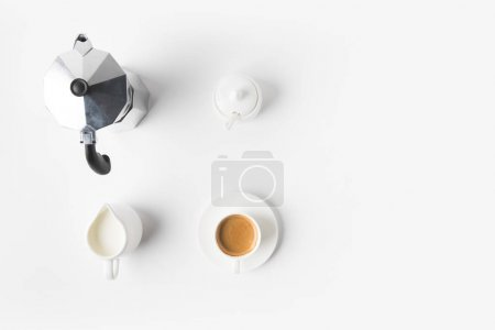 Photo for Top view of arranged cup of coffee, jag of milk and coffee maker on white surface - Royalty Free Image