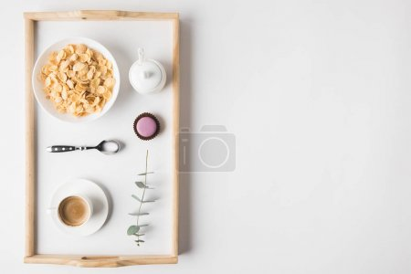 Photo for Top view of breakfast with cork flakes in bowl and cup of coffee on tray on white surface - Royalty Free Image