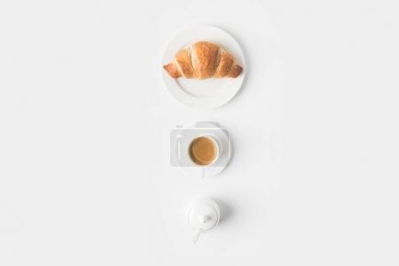 Photo for Top view of cup of coffee and croissant for breakfast on white surface - Royalty Free Image