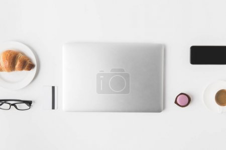 flat lay with digital devices, eyeglasses and breakfast on white tabletop