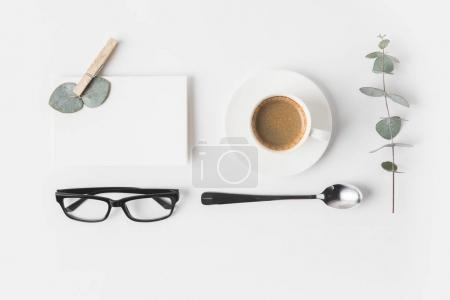 Photo for Top view of eyeglasses, cup of coffee, napkin and plant on white surface - Royalty Free Image