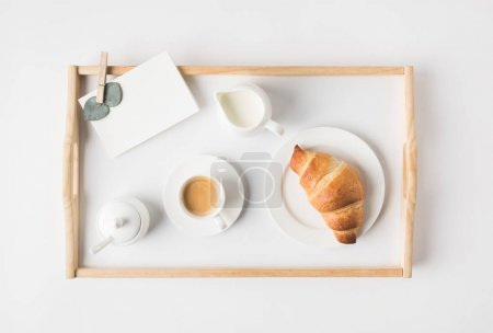 Photo for Flat lay with cup coffee and croissant for breakfast on tray on white tabletop - Royalty Free Image