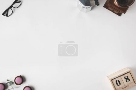 top view of arrangement of calendar, eyeglasses, desserts and coffee maker on white surface