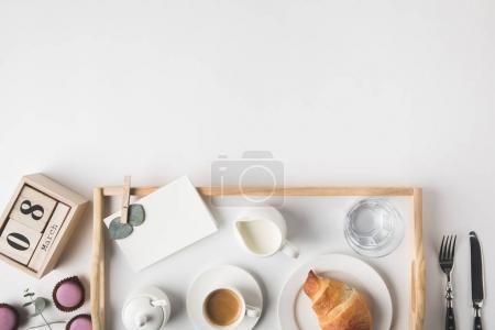 flache Liege mit Tasse Kaffee und Croissant zum Frühstück auf Tablett auf weißer Tischplatte