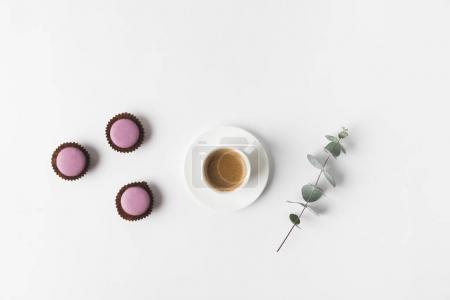 Draufsicht auf arrangierte Tasse Kaffee, Desserts und Pflanze auf weißer Tischplatte