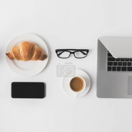 Photo for Flat lay with digital devices, eyeglasses and breakfast on white tabletop - Royalty Free Image