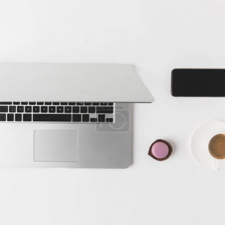 flat lay with laptop, smartphone, cup of coffee and dessert on white tabletop
