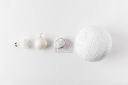 various sports equipment andonion in row on white surface