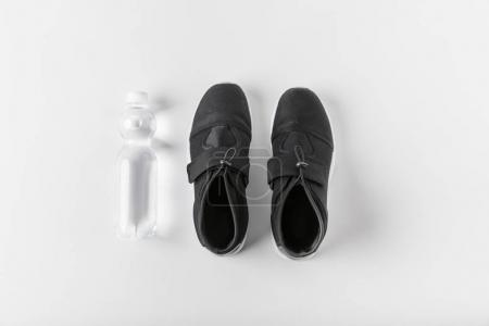 top view of water bottle and sneakers on white surface