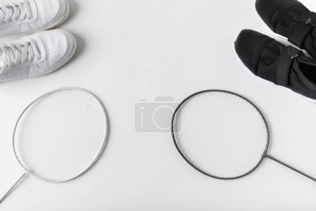 top view of badminton rackets and sneakers on white surface