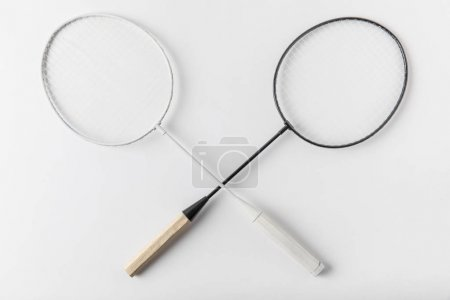 top view of crossed badminton rackets on white surface