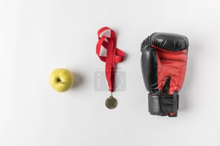 top view of boxing glove with medal and green apple on white surface