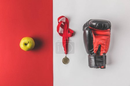 Photo pour Vue de dessus du gant de boxe avec médaille et pomme sur le dessus de table rouge et blanc - image libre de droit