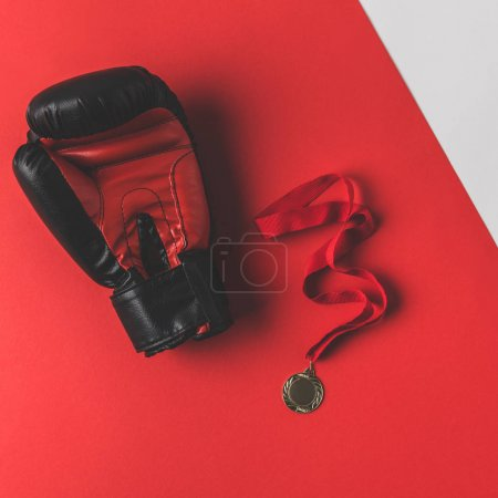top view of boxing glove with medal on red surface