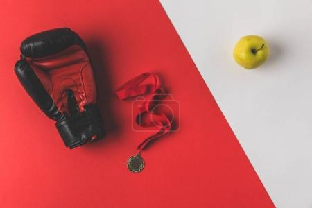 top view of boxing glove with medal and apple on red and white surface