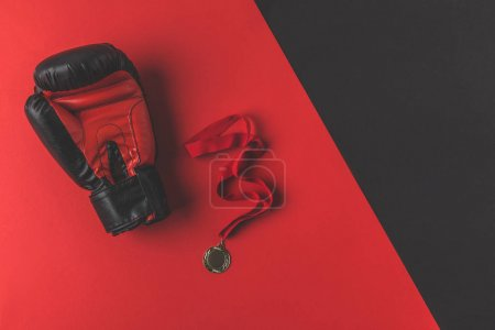 top view of boxing glove with medal on red and black surface