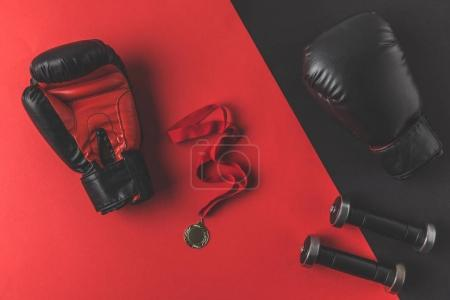 top view of boxing gloves with medal and dumbbells on red and black surface