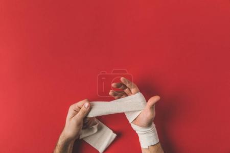 cropped shot of fighter covering up hands in elastic bandage before fight on red surface