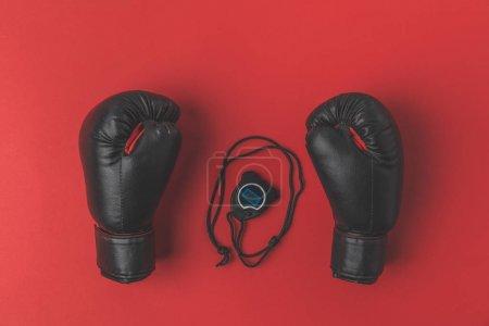 Photo pour Vue de dessus des gants de boxe avec chronomètre sur table rouge - image libre de droit