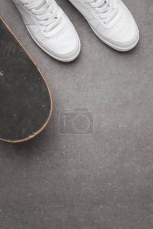 Photo for Top view of white sneakers and skateboard on gray asphalt surface - Royalty Free Image