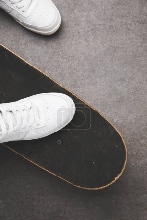 top view of white shoes on skateboard on gray concrete surface