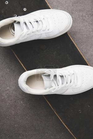 top view of white sneakers on skateboard on concrete surface