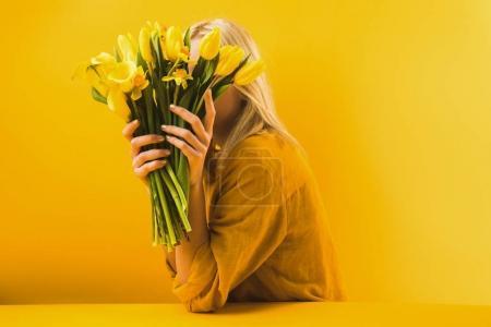 Photo pour Jeune femme tenant de belles fleurs jaunes de printemps sur jaune - image libre de droit