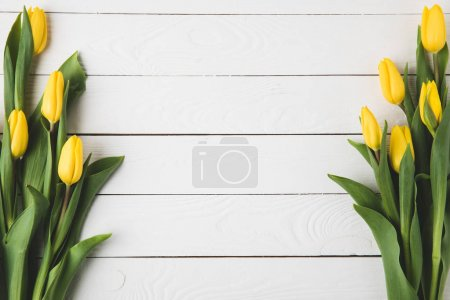 Photo for Top view of beautiful yellow tulip flowers on white wooden surface - Royalty Free Image
